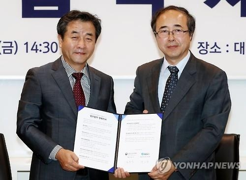 Yonhap News Agency CEO Park No-hwang (L) and Kim Yong-jick (R), director of the National Museum of Korean Contemporary History, pose for a photo after signing a memorandum of understanding for content sharing in Seoul on Sept. 9, 2016. (Yonhap)