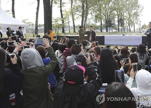 Fans take photos of Ryeowook, a member of the popular boy group Super Junior, at a meeting that took place before the singer enters the military on Oct. 11, 2016. (Yonhap)