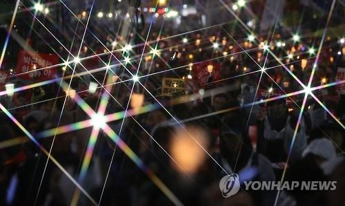 Protesters hold up candles at Gwanghwamun Square in central Seoul on Nov. 26, 2016, to call for President Park Geun-hye's resignation. Park has been under pressure to step down over a nation-rocking political scandal involving her and her longtime confidante Choi Soon-sil. (Yonhap)