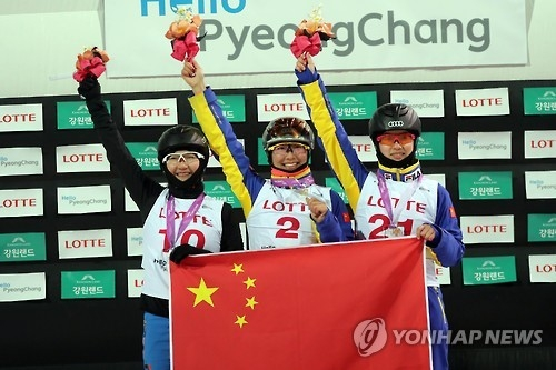 Chinese aerial skiers Xu Mengtao (C), Shen Xiaoxue (L), and Yang Yu hold their national flag at the medal ceremony at the FIS Freestyle Ski World Cup in PyeongChang, Gangwon Province, on Feb. 10, 2017. (Yonhap)