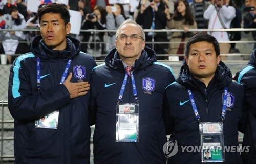 South Korean men's national football team head coach Uli Stielike (C) listens to the national anthem ahead of the 2018 FIFA World Cup qualifying match between South Korea and Syria at Seoul World Cup Stadium in Seoul on March 28, 2017. (Yonhap)