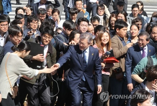 Moon Jae-in (C), the presidential candidate of the liberal Democratic Party, shakes hands with a female supporter while visiting Gwanghwamun Square, the venue of weekly candlelight vigils in downtown Seoul that helped propel the recent ouster of former President Park Geun-hye, on April 10, 2017. (Yonhap)