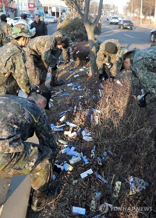 This file photo, taken on Feb. 9, 2017, shows South Korean soldiers picking up North Korean propaganda leaflets on a street in Goyang, northwest of Seoul. (Yonhap)