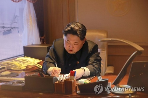 "In this image captured on Feb. 7, 2016, from the North's Korean Central TV Broadcasting Station, North Korean leader Kim Jong-un signs an order on the previous day to launch the ""Kwangmyongsong-4"" satellite. (For Use Only in the Republic of Korea. No Redistribution) (Yonhap)"