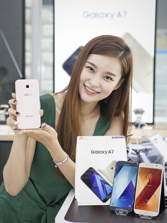 A model poses with Samsung Electronics Co.'s Galaxy A7 smartphone in this photo released by SK Telecom Co. on July 12, 2017. (Yonhap)