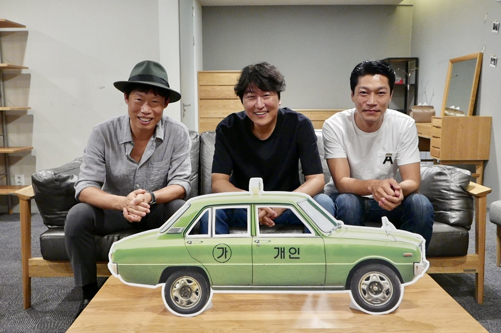 "In this photo released by Showbox, three members of the main cast of ""A Taxi Driver"" -- Yoo Hae-jin, Song Kang-ho and Choi Gui-hwa (L to R) -- pose for the camera in celebration of the film attracting over 8 million viewers. (Yonhap)"