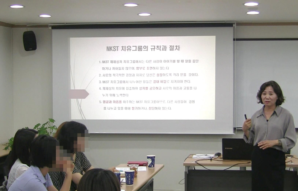 This photo, provided by the North Korea System Trauma Healing and Counseling Center on Sept. 28, 2017, shows Yoo Hye-ran (R), the head of the center, speaking to North Korean defectors who want to relieve their psychological pain through a six-month counseling program. (Yonhap)