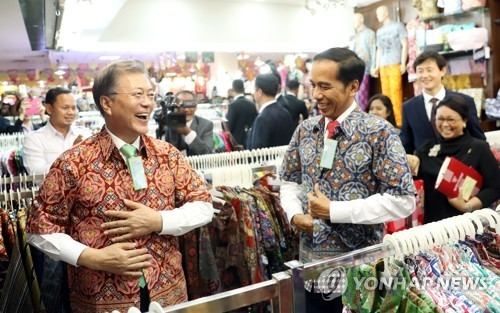 South Korean President Moon Jae-in (L) smiles after putting on a batik shirt, which Indonesian President Joko Widodo (second from L) purchased at a local mall near Bogor Palace, in Bogor, south of Jakarta, as a surprise gift for the visiting South Korean leader before their bilateral summit in Jakarta on Nov. 9, 2017. (Yonhap)