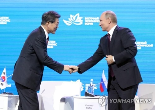 South Korean President Moon Jae-in (L) shakes hands with Russian President Vladimir Putin at the Eastern Economic Forum in Vladivostok, Russia, on Sept. 7, 2017. (Yonhap)