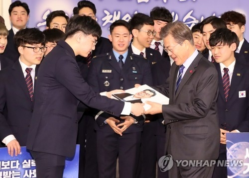 President Moon Jae-in (R) receives a caricature of himself as a gift from the South Korean team that competed at the World Skills Competition, held in Abu Dhabi in October, before the start of a special lunch with the team at his office Cheong Wa Dae in Seoul on Dec. 1, 2017. (Yonhap)