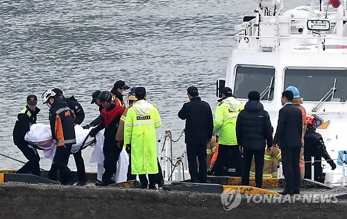 Coast Guard officials carry the body of a victim of the fishing boat accident that happened near Incheon on Dec. 3, 2017. (Yonhap)