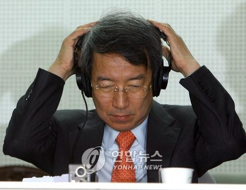 In this file photo taken on March 30, 2008, Chung Un-chan, former prime minister named the new commissioner of the Korea Baseball Organization (KBO), puts on a headset to provide commentary on a KBO regular season game between the Woori Heroes and the Doosan Bears at Jamsil Stadium in Seoul. (Yonhap)