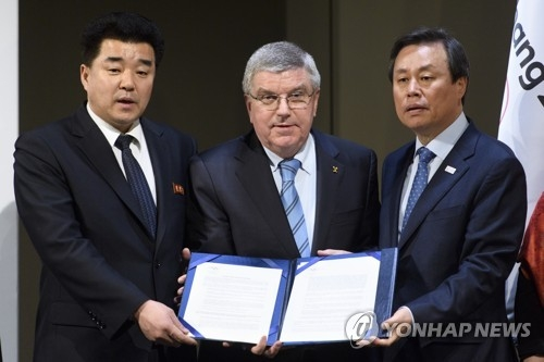 In this Associated Press photo, International Olympic Committee (IOC) President Thomas Bach (C), North Korean Sports Minister Kim Il-guk (L) and South Korean Sports Minister Do Jong-hwan hold up documents after a signing ceremony for the IOC's North and South Korean Olympic Participation Meeting at the IOC headquarters in Lausanne, Switzerland, on Jan. 20, 2018. (Yonhap)
