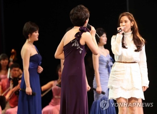 In this file photo, Seohyun (R), a former member of S.M. Entertainment's idol group Girls' Generation, sings with North Korean musicians during a concert by a North Korean art troupe in Seoul on Feb. 11, 2018. (Yonhap)