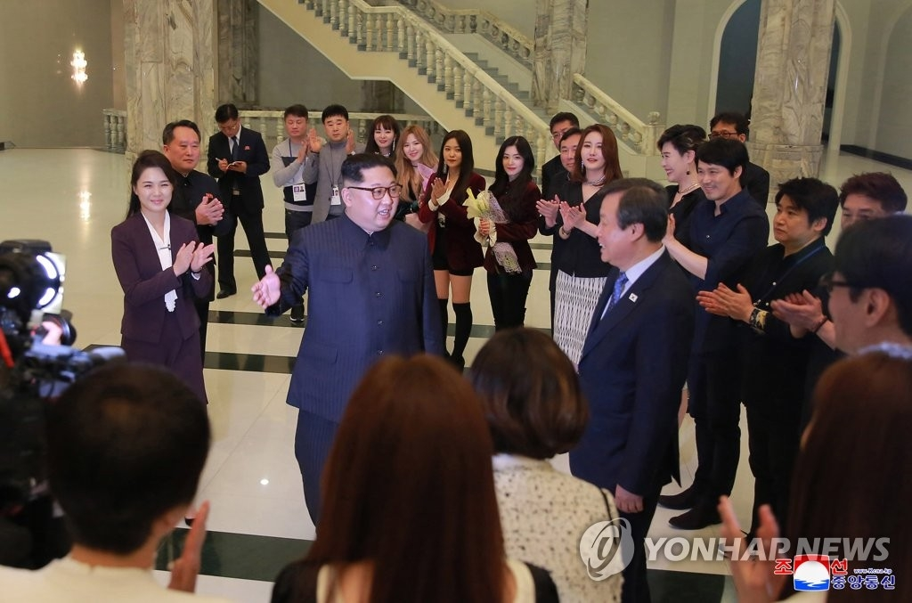 This photo released by the North Korea's state-run Korean Central News Agency (KCNA) shows North Korean leader Kim Jong-un (C) together with his wife Ri Sol-ju, conversing with South Korean culture minister Do Jong-whan after enjoying a performance by a South Korean art troupe at the East Pyongyang Grand Theatre in Pyongyang on April 1, 2018. (Yonhap)