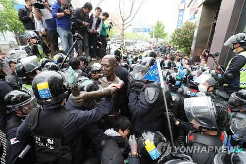 Police block activists from moving a statue symbolizing Korean victims of forced labor under Japan's colonial rule in Busan on May 1, 2018. (Yonhap)
