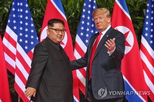 This photo, provided by the Singaporean government, shows North Korean leader Kim Jong-un (L) and U.S. President Donald Trump meeting at the Capella Hotel on Sentosa Island on June 12, 2018. (Yonhap)