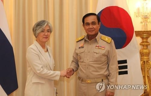 Foreign Minister Kang Kyung-wha shakes hands with Thai Prime Minister Prayut Chan-o-cha during their meeting in Bangkok on July 2, 2018. (Yonhap)
