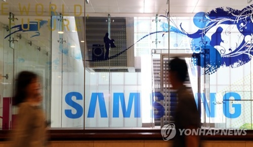Pedestrians pass by Samsung Electronics Co.'s logo at the company's building in Seoul on July 6, 2018. (Yonhap)