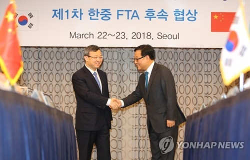 Kim Young-sam (R), a deputy minister of trade and investment at South Korea's Ministry of Trade, Industry and Energy, shakes hands with Wang Shouwen (L), vice Chinese commerce minister, during the first round of follow-up negotiations for the countries' bilateral trade agreement in Seoul on March 22, 2018. (Yonhap)