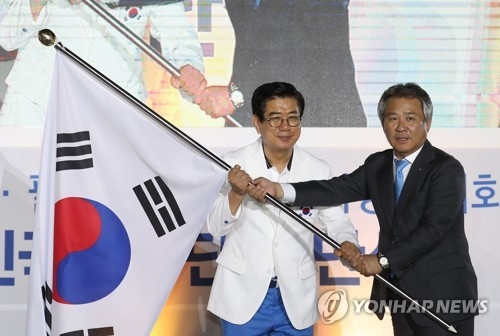 Korean Sport & Olympic Committee President Lee Kee-heung (R) hands over the South Korean national flag, the Taegeukgi, to Kim Seong-jo, the chief South Korean delegate to the 2018 Asian Games, during the team launch ceremony at SK Olympic Handball Gymnasium in Seoul on Aug. 7, 2018. The Asian Games will be held from Aug. 18 to Sept. 2 in Jakarta and Palembang, Indonesia. (Yonhap)