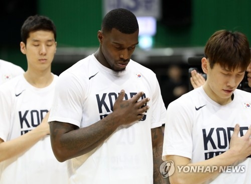 In this file photo from Feb. 23, 2018, Ricardo Ratliffe (C), a U.S.-born South Korean basketball player, stands for the national anthem before South Korea's game against Hong Kong in the Asian qualifying round for the 2019 FIBA Basketball World Cup at Jamsil Gymnasium in Seoul. Ratliffe acquired his South Korean passport in January 2018 and will represent South Korea at the Aug. 18-Sept. 2 Asian Games in Jakarta and Palembang, Indonesia. (Yonhap)