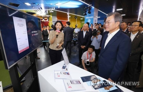 President Moon Jae-in looks at an Internet banking account opening at an event at Seoul City Hall in downtown Seoul on Aug. 7, 2018, to promote Internet banks. (Yonhap)
