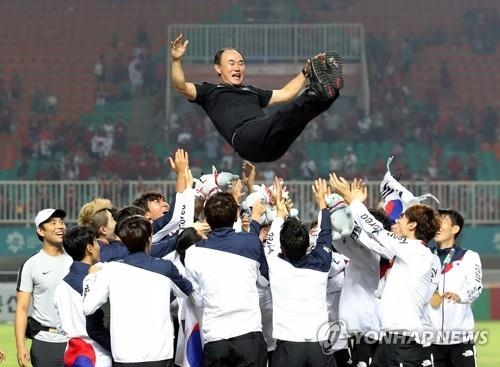 In this file photo, taken Sept. 1, 2018, South Korea's under-23 national football team head coach Kim Hak-bum (C) is tossed up in the air by his players after winning a gold medal at the 18th Asian Games at Pakansari Stadium in Cibinong, Indonesia. (Yonhap)