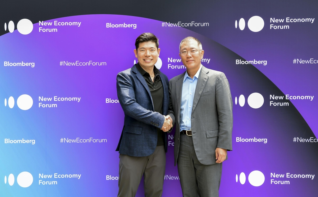 In this photo taken on Nov. 6, 2018, and provided by the Bloomberg New Economy Forum, Hyundai Motor Group Vice Chairman Chung Eui-sun (R) shakes hands with Anthony Tan, founder and CEO of Grab, at a Singapore hotel during the Bloomberg forum. (Yonhap)