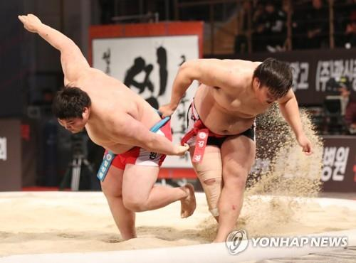 Two people wrestle in a ssireum match on sand in this file photo. (Yonhap)