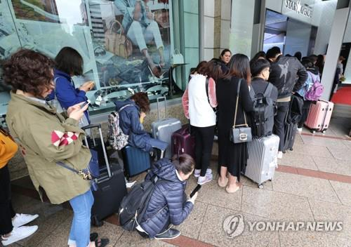This file photo shows Chinese shoppers waiting in line to buy goods at a local duty free store in Seoul. (Yonhap)