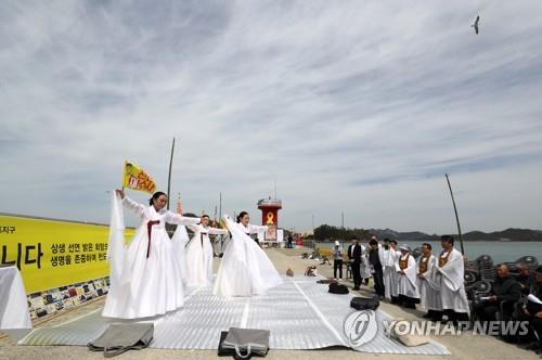 Marking the fifth anniversary of the sinking of the Sewol ferry, a religious group holds a memorial event at the port of Paengmok on the southwestern coast on April 16, 2019. (Yonhap)