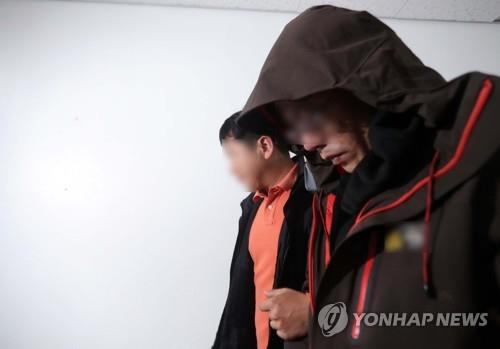 The suspect (R) in an apartment arson and murder case in Jinju, South Gyeongsang Province, is escorted by a police officer at the Jinju Police Station on April 17, 2019. (Yonhap)