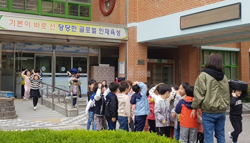This photo shows students evacuating their classrooms to assemble in the playground of an elementary school in the city of Gangneung on South Korea's east coast on April 19, 2019, after a magnitude 4.3 earthquake struck off the east coast near the city of Donghae. (Yonhap)