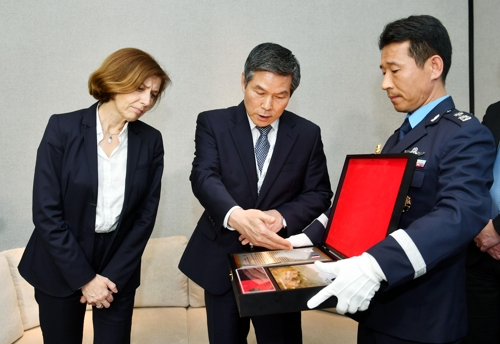 South Korean Defense Minister Jeong Kyeong-doo (C) talks about the dog tag of a French medic who died during the Korean War to his French counterpart, Florence Parly (L), during their bilateral talks in Singapore on June 1, 2019. (Yonhap)