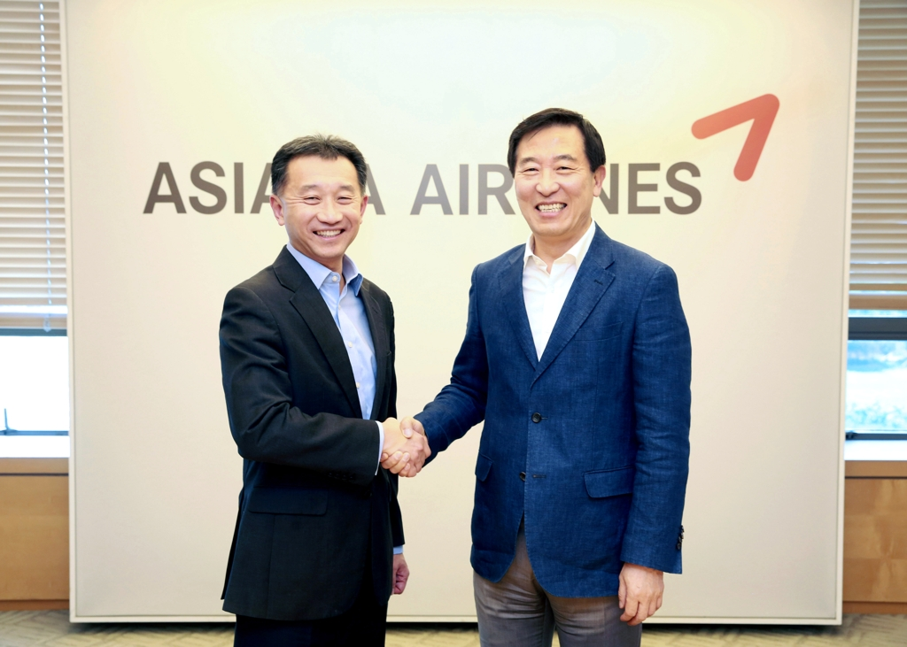 In this photo provided by Asiana Airlines Inc., Jeffery Goh (L), the CEO of Star Alliance Services GmbH, shakes hands with Asiana Airlines CEO Han Chang-soo at a Seoul hotel on June 1, 2019. (Yonhap)
