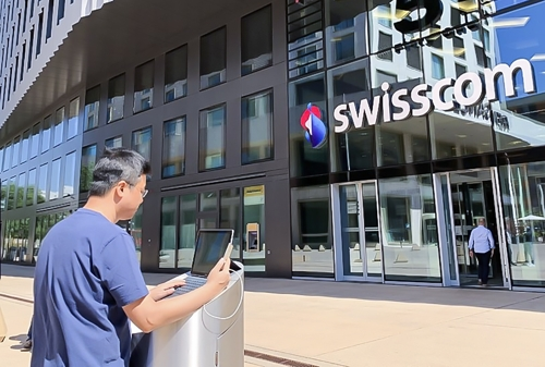 An employee of SK Telecom Co. tests 5G roaming service in front of Swisscom's building in Switzerland in this photo provided by the South Korean telecom operator on July 16, 2019. (PHOTO NOT FOR SALE) (Yonhap)