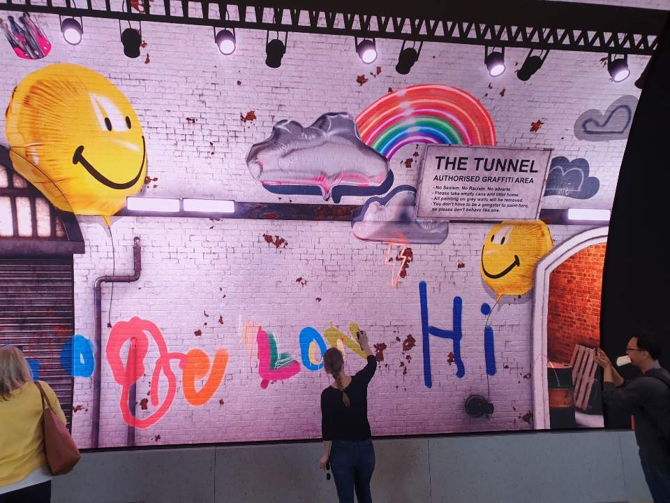 A visitor paints on a digital graffiti wall with a Galaxy S10 smartphone at Samsung KX in London on Sept. 8, 2019. (Yonhap)