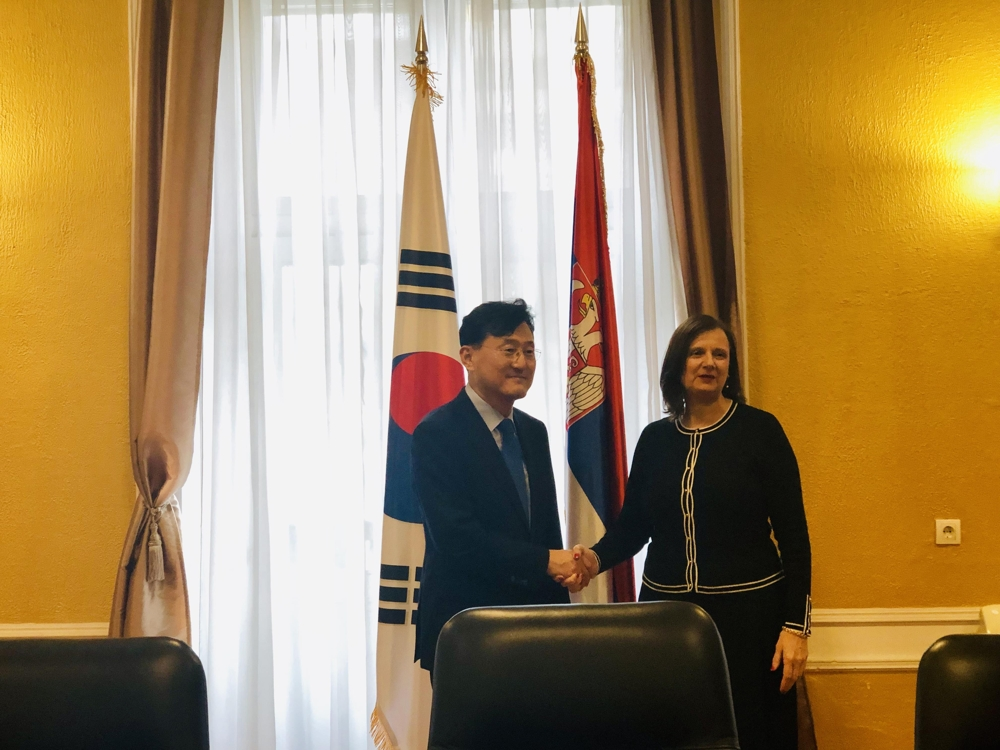 In this photo provided by Seoul's foreign ministry, Deputy Foreign Minister for Political Affairs Yoon Soon-gu shakes hands with his Serbian counterpart, Tatjana Conic, assistant minister for bilateral affairs, ahead of their meeting in Belgrade, on Oct. 3, 2019. (Yonhap)