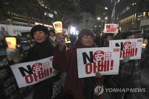This AP photo shows protesters holding a candlelight vigil to demand the abolishment of the General Security of Military Information Agreement, or GSOMIA, an intelligence-sharing agreement between South Korea and Japan, near the Japanese Embassy in Seoul on Nov. 16, 2019. (Yonhap)