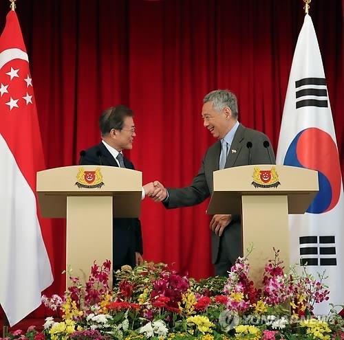 In this file photo, dated July 12, 2018, Singapore's Prime Minister Lee Hsien Loong (R) shakes hands with South Korean President Moon Jae-in after a joint press conference in the city-state. (Yonhap)