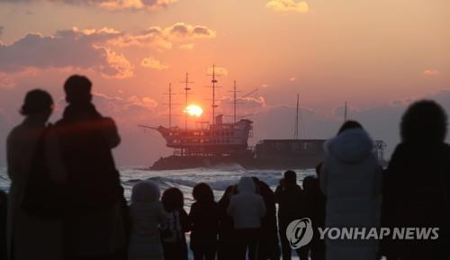 This file photo taken on Dec. 20, 2019, shows people watching sunrise on Jeongdongjin Beach in Gangneung, Gangwon Province. (Yonhap)
