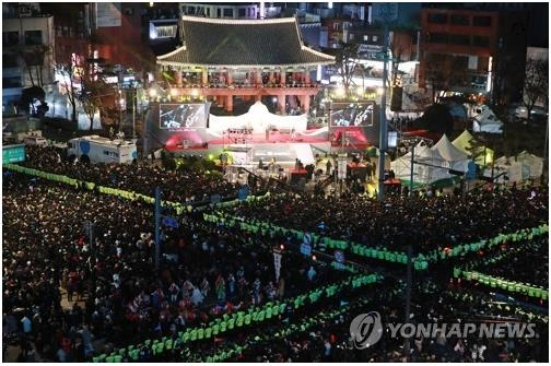 People gather in front of the Bosingak Belfry in central Seoul on Dec. 31, 2019, to watch the traditional bell-ringing ceremony that takes place at midnight. (Yonhap)