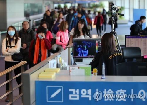 A quarantine official (R) checks passengers arriving at South Korea's Incheon International Airport for signs of fever and other symptoms in this file photo taken on Jan. 9, 2020. (Yonhap)
