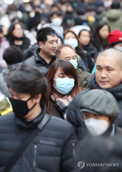 Pedestrians wearing facial masks walk down the streets of Myeongdong in central Seoul on Jan. 28, 2020. (Yonhap)