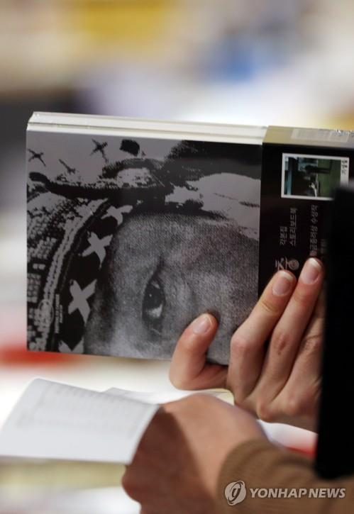 "A reader holds a set of ""Parasite"" scenario and storyboard books at a Seoul book store on Feb. 11, 2020. (Yonhap)"