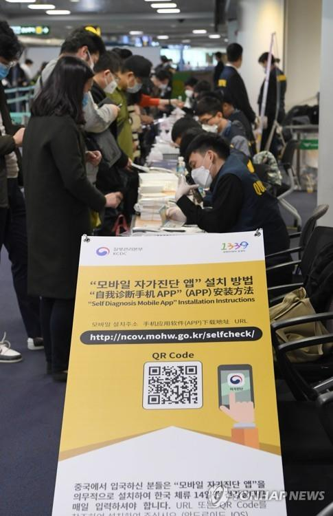 Tourists from China, Hong Kong and Macao install an application on their smartphones that the health ministry has released to help people check if they have the new COVID-19 coronavirus with the help of airport officials at the arrival gate of Incheon International Airport, west of Seoul, on Feb. 13, 2020. (Pool photo) (Yonhap)