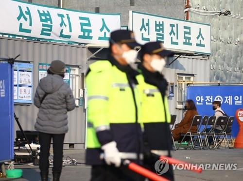 Police officers wearing masks stand guard at a medical center in Daegu, 300 kilometers southeast of Seoul, on Feb. 20, 2020, as people suspected of having been infected with the new coronavirus arrive to receive tests. (Yonhap)