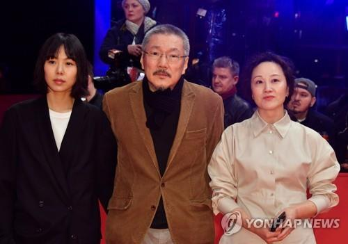 "In this AFP photo, South Korean director Hong Sang-soo (C) of ""The Woman Who Ran"" and actresses Kim Min-hee (L) and Seo Young-hwa (R) pose on the red carpet ahead of the awards ceremony of the 70th Berlinale film festival in Berlin on Feb. 29, 2020. (Yonhap)"