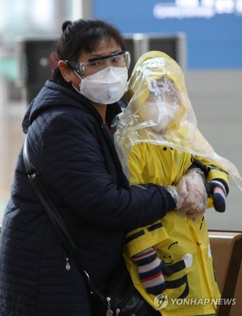 A Chinese mother wearing goggles and a mask and clutching her raincoat-clad child waits in the departure lounge of Incheon airport, west of Seoul, on March 4, 2020, amid concern about the spread of the new coronavirus. (Yonhap)